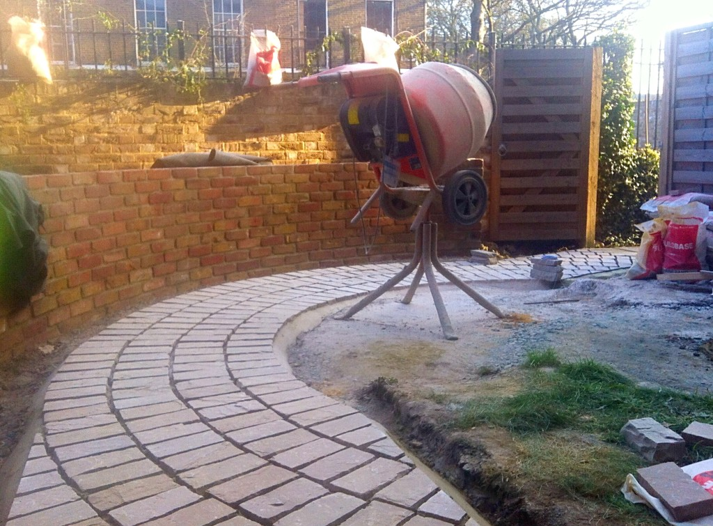 paving the curved path with sandstone setts